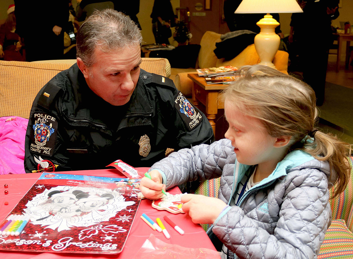 Policeman at table, talking with a young child at a holiday party.
