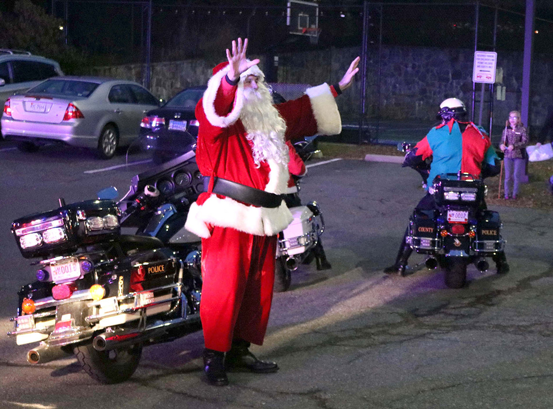 Santa Claus gets off his Harley-Davidson motorcycle upon his arrival at Children's Inn.