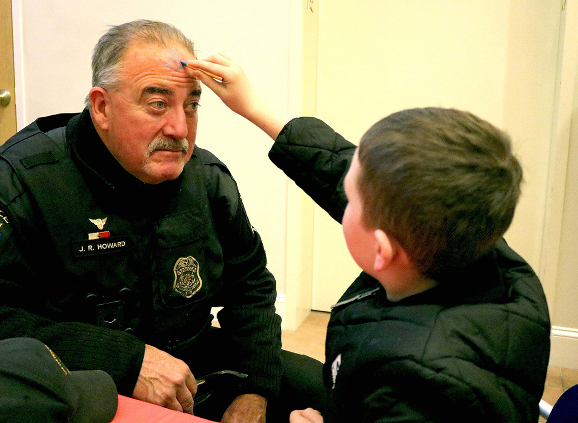 A youngster paints the face of a police officer at a holiday party.