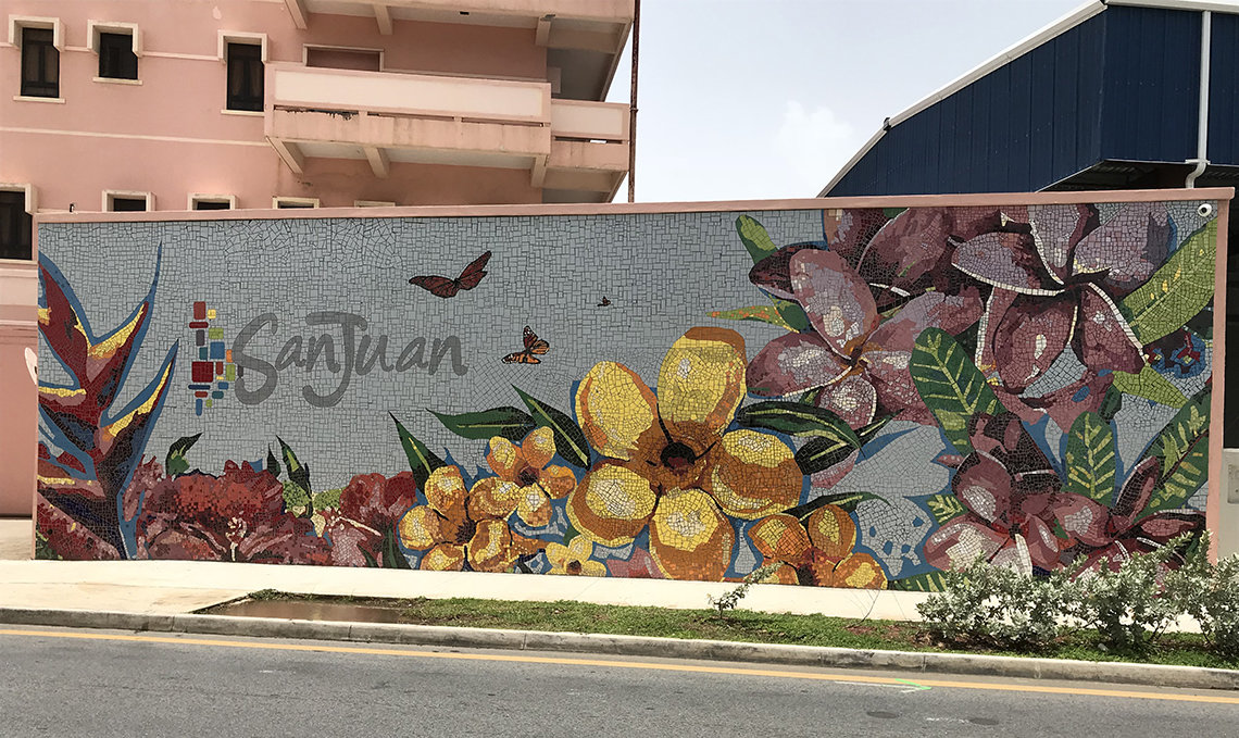 A mural of yellow and pink flowers graces a city wall in San Juan, Puerto Rico