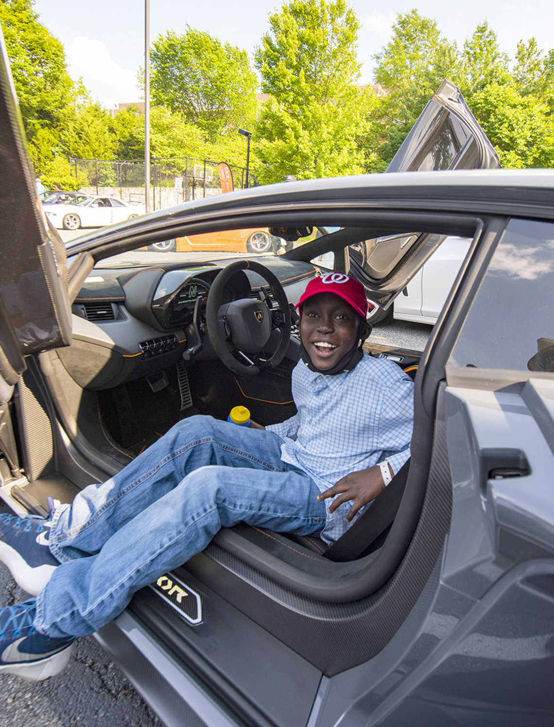 Smiling youngster sits in the driver's seat of a luxury sportscar.