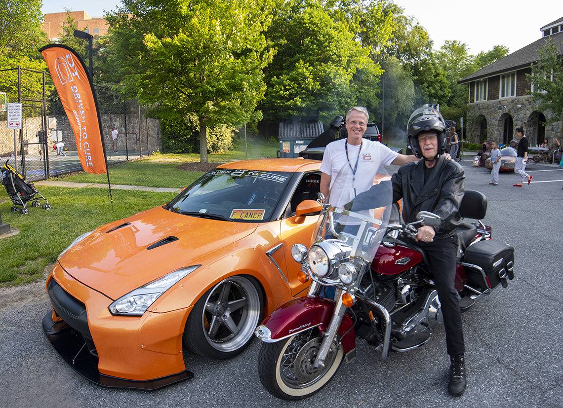 In front of Nissan GTR sportscar, Lee smiles with Collins on motorcycle