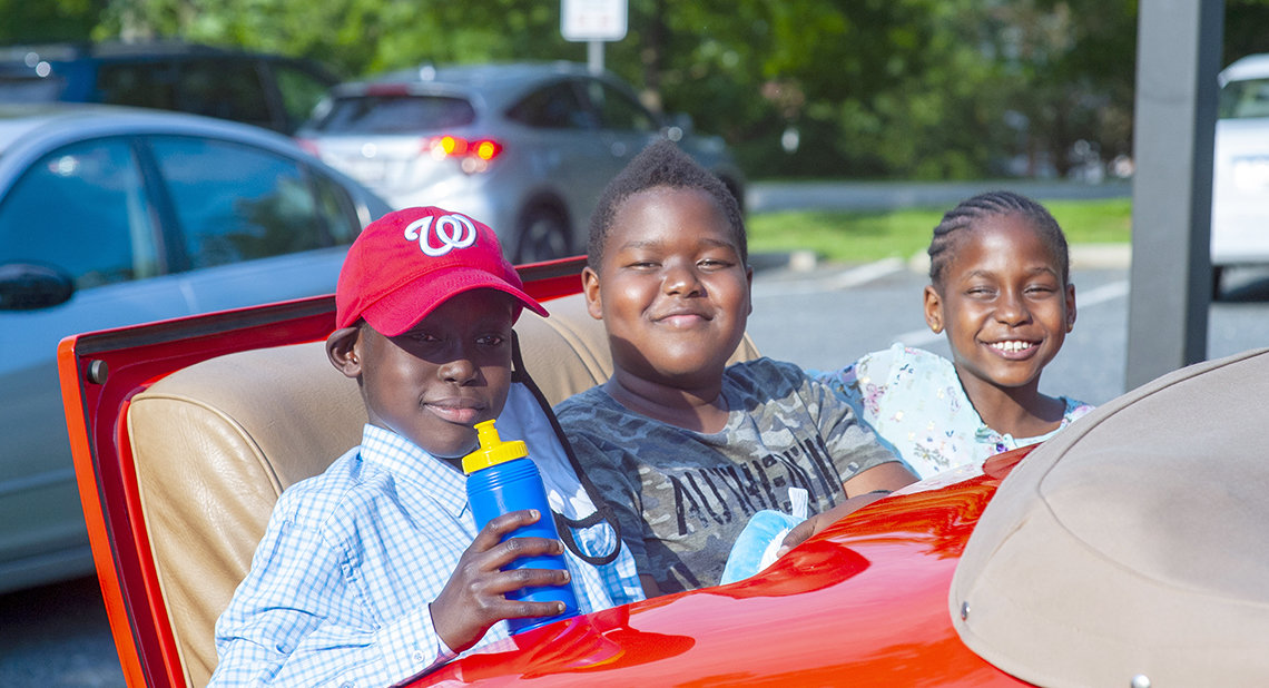 Kids smiling in rumble seat of Cadillac