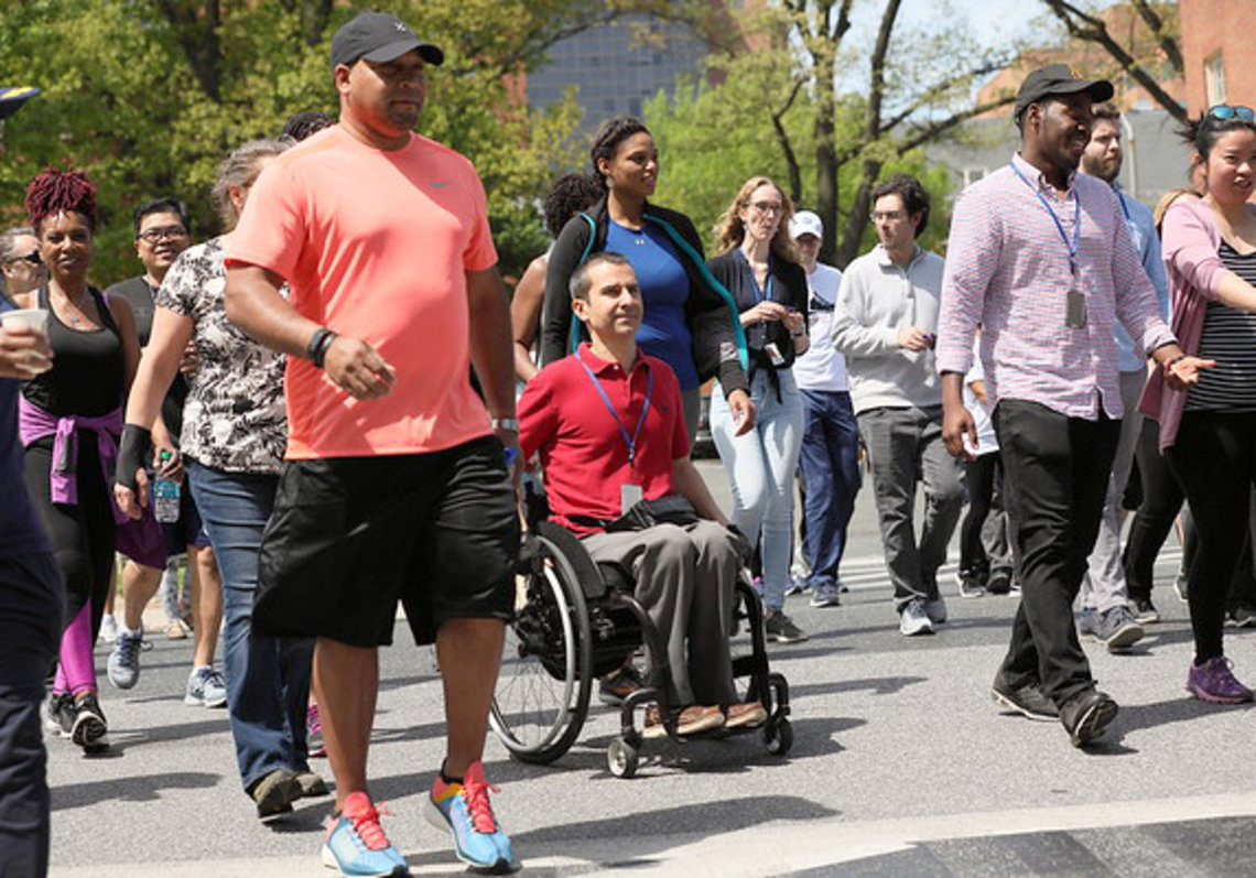 Participant using wheelchair amid walkers starting 5K