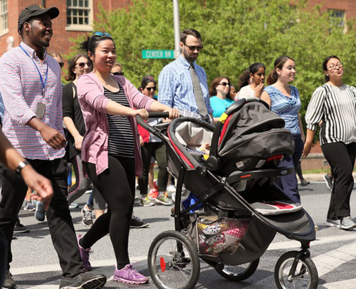 Amid other walkers, woman pushes stroller