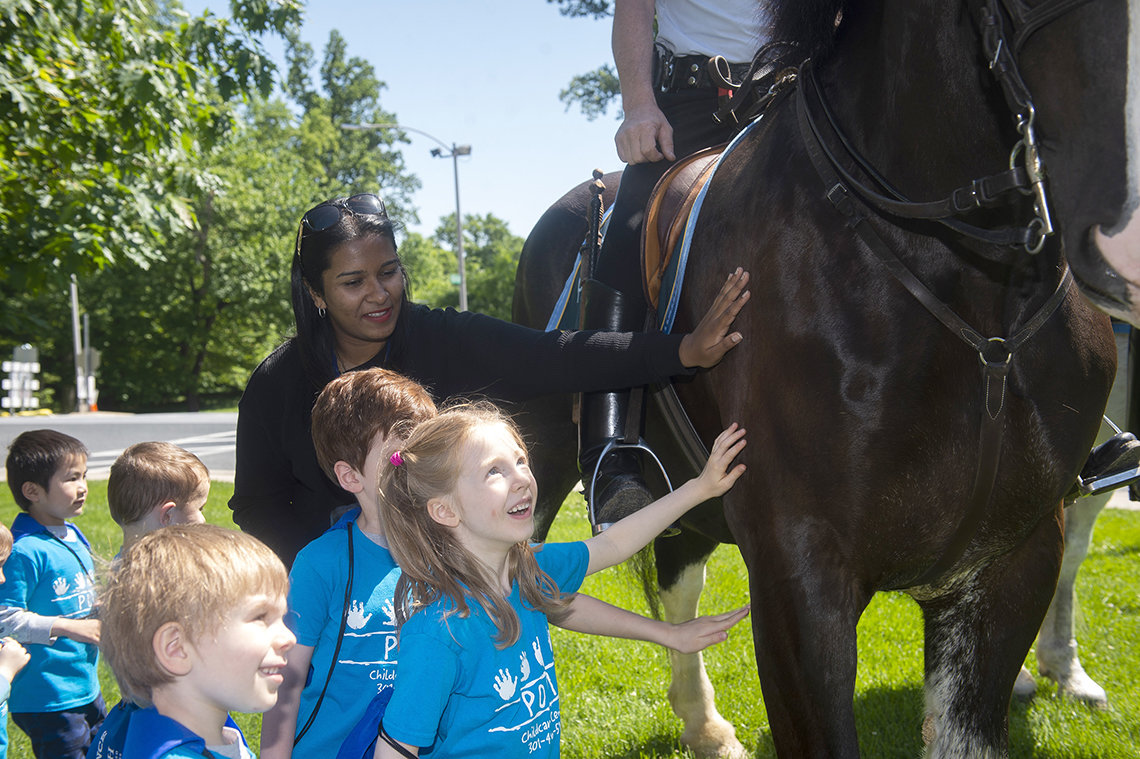 Kids visit with officers on horseback.
