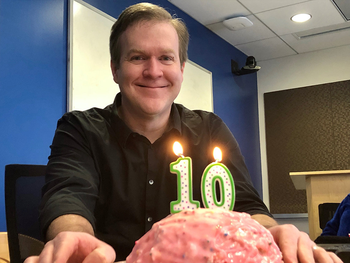 "McGavern smiles behind brain-shaped cake with ""1"" and ""0"" candles"