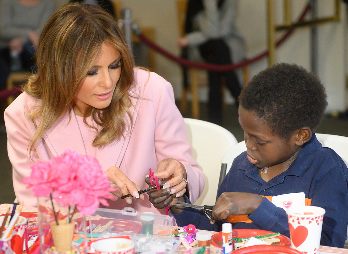 First Lady Trump helps young inn resident use craft scissors and ribbon