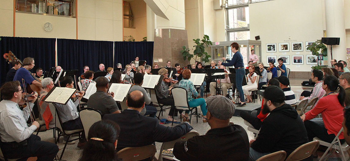 Dozens of musicians shown from behind, in the large, open atrium of the Clinical Center