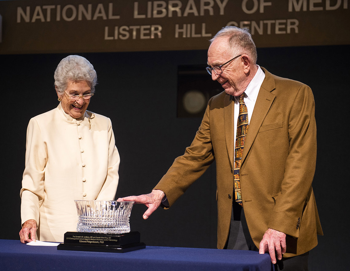 Mary Lindberg and Dr. Feigenbaum both smile as he admires, points to crystal bowl lecture award in Lister Hill Center.