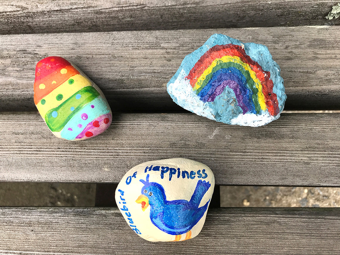 Three painted rocks on a bench, including a drawing of the bluebird of happiness.