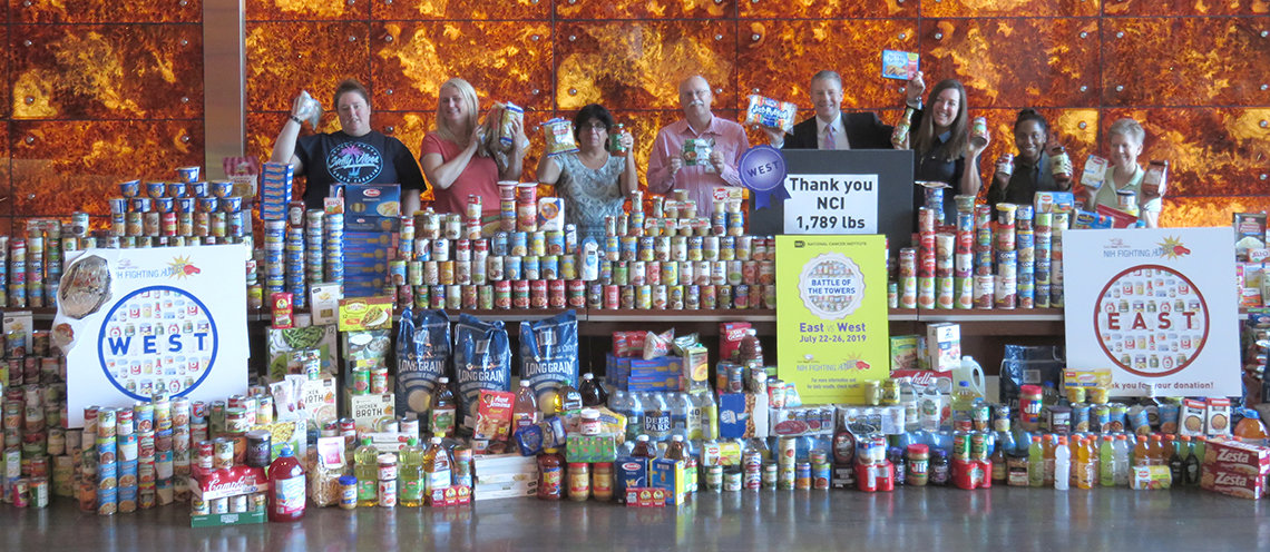 Volunteers display a huge wall of canned foods.
