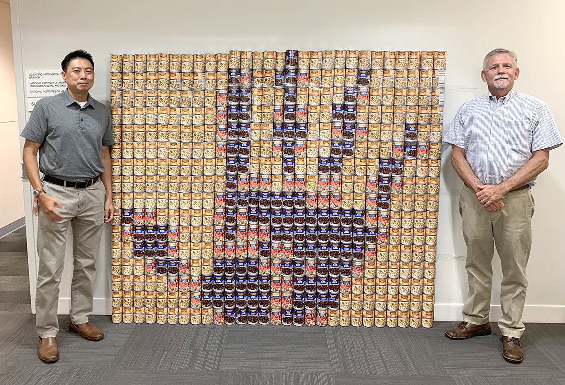Two men stand beside an image of a hand, made of food cans.