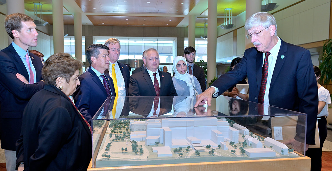 Collins points to the Clinical Center model in the CRC atrium while talking with Members of Congress.