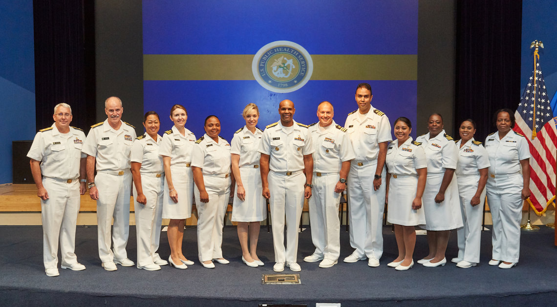 Dressed in their white uniforms, recently promoted NIH Commissioned Corps officers pose with the surgeon general.