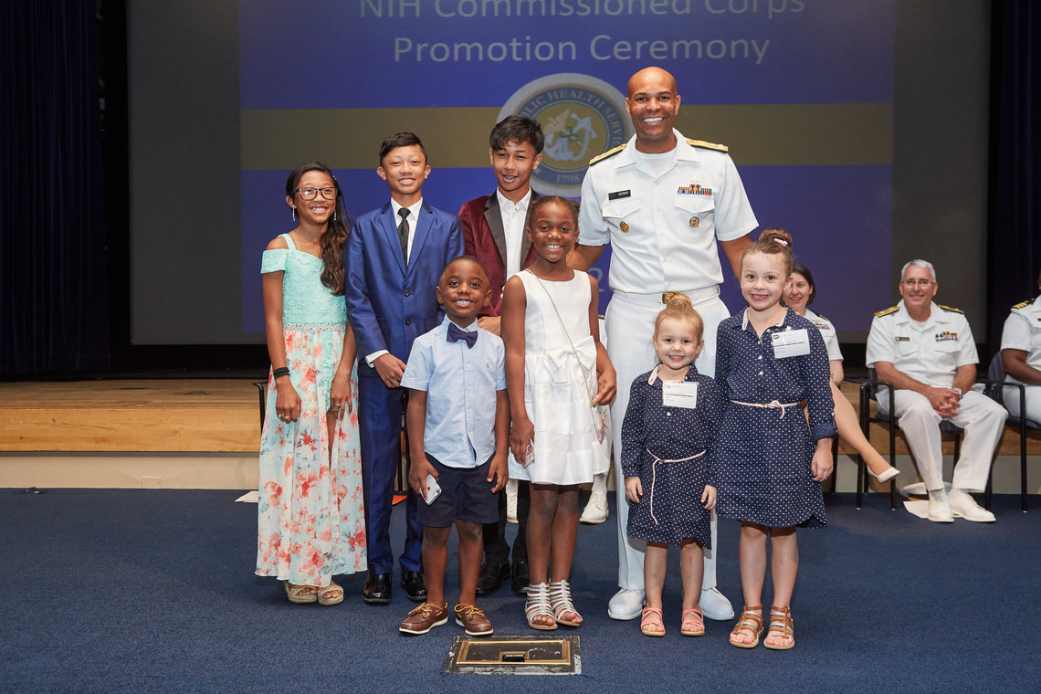 Children pose on stage with Surgeon General Jerome Adams
