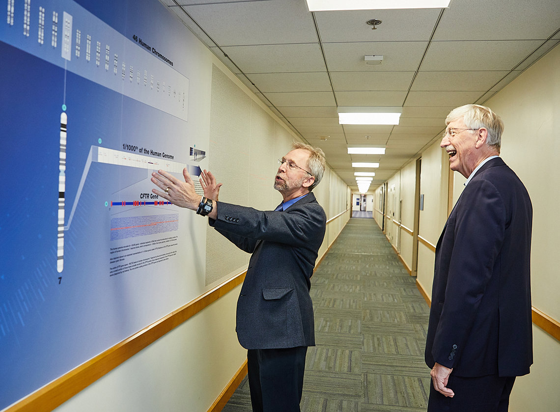 Dr. Green holds his hands up to wall of genome hallway exhibit as Dr. Collins marvels at the display.