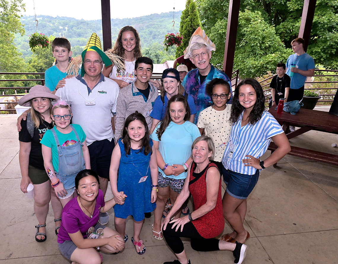 Group of children pose outside with Dr. Collins and his wife at Camp Fantastic.