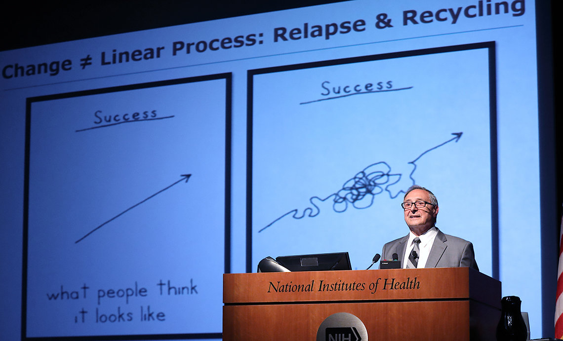 DiClimente talks in front of slide that shows squiggly line of conquering addiction, illustrating that success is not linear.