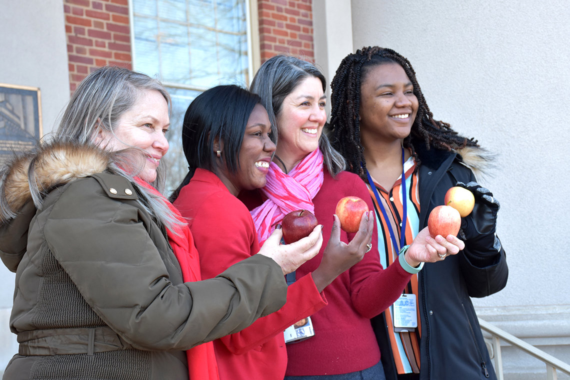 Four women smile as they hold up apples.