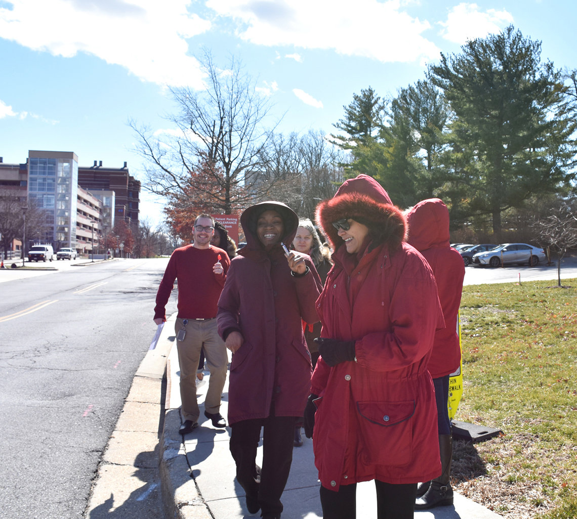 Several people walk across campus while wearing red.