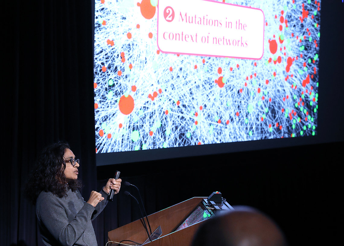 Singh speaks in front of a slide