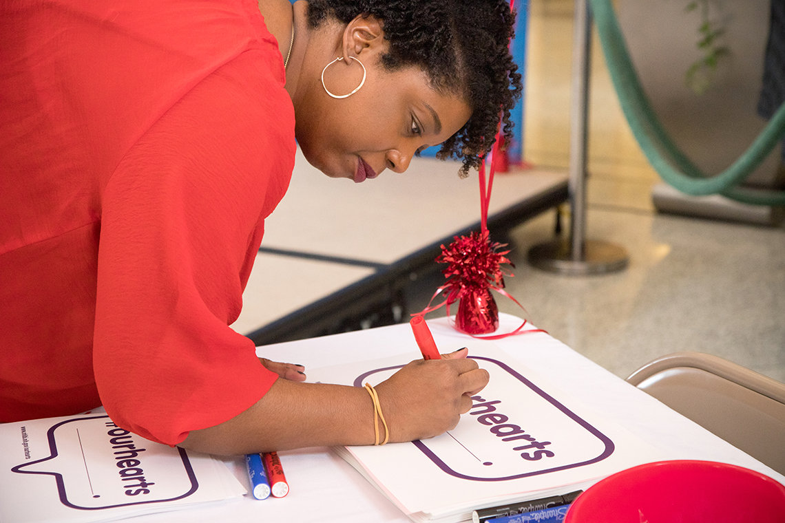 Woman leans over table to sign a poster-size pledge card.