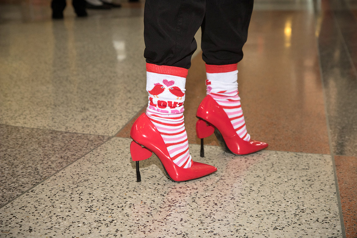Close-up of red high-heeled shoes with heart shapes on the heels