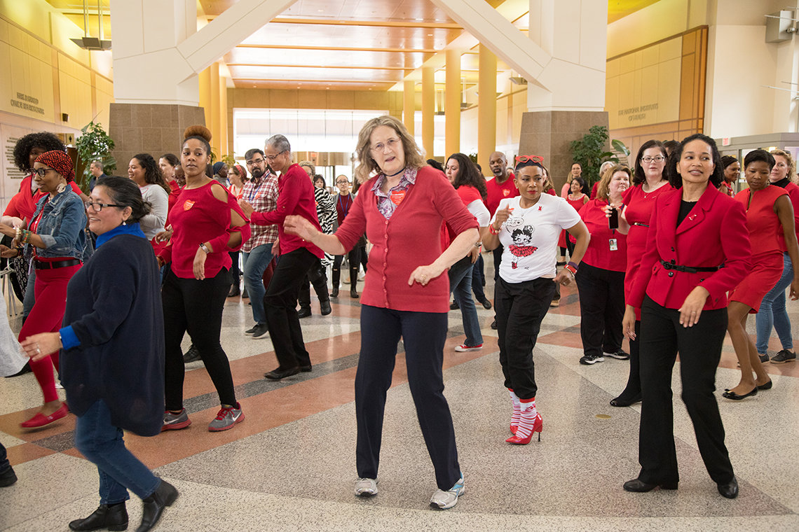 Large group of people dressed in red, dancing.