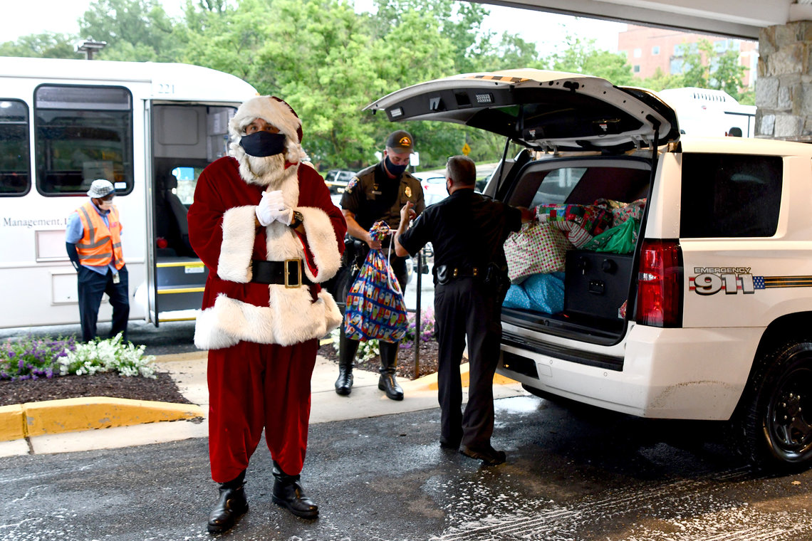 A police officer dressed as Santa arrives at the Children's Inn with bags full of presents for the kids.