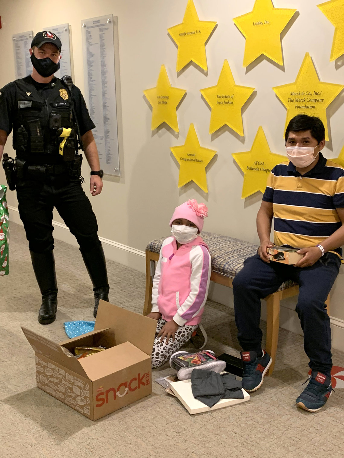Police officer watches a young patient open presents