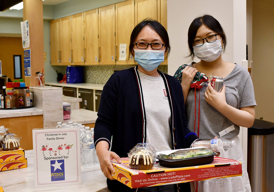 A young adult and her mom, smiling behind their masks, hold a pizza box, salad and cake.
