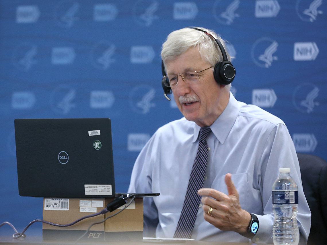 Collins wearing headset sits in front of computer screen