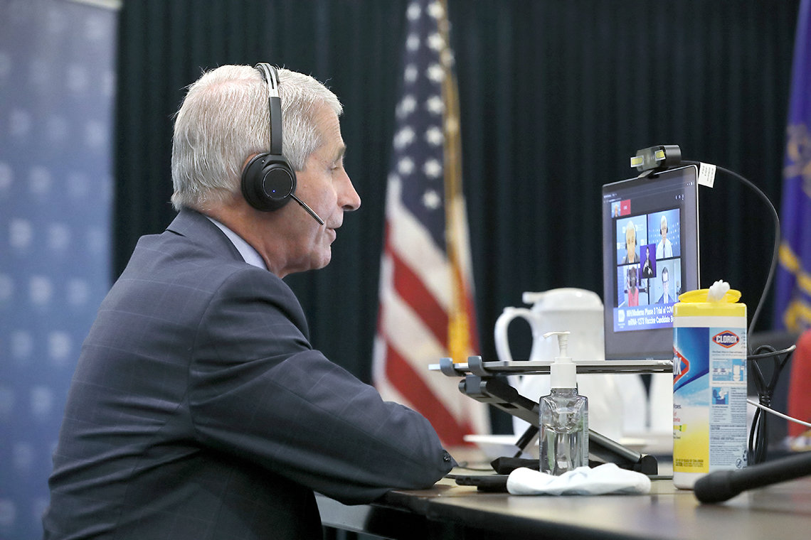 Fauci wearing headset sits in front of computer screen