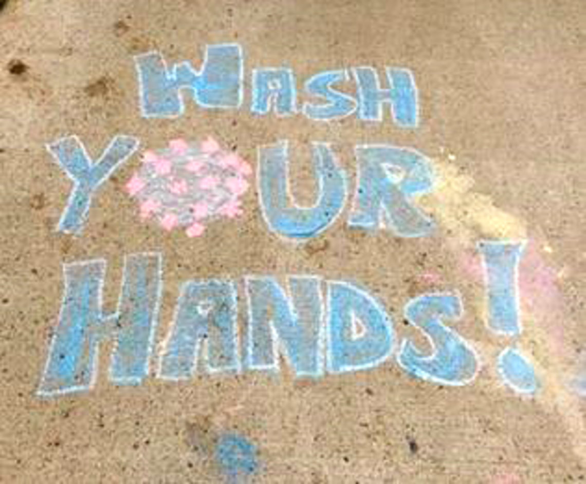 """The phrase, """"wash your hands!"""" written in chalk"""