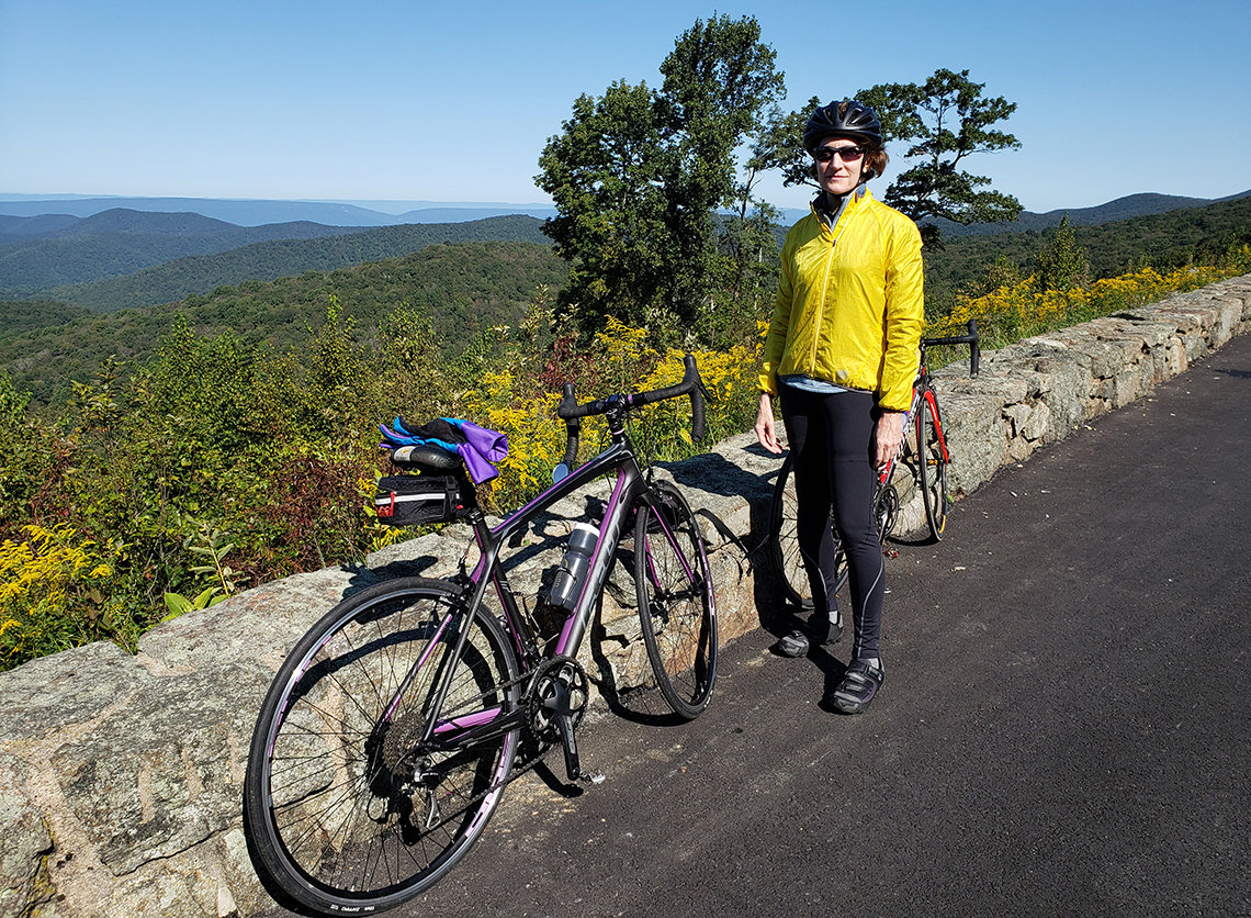 Marill next to her bike surrounded by the hills and foliage of Skyline Drive in Virginia