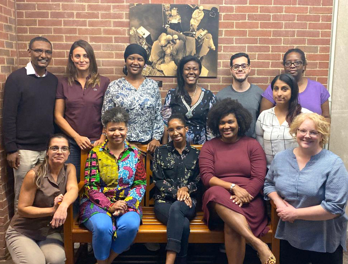 Dr. Paule Joseph, surrounded by 11 smiling colleagues.