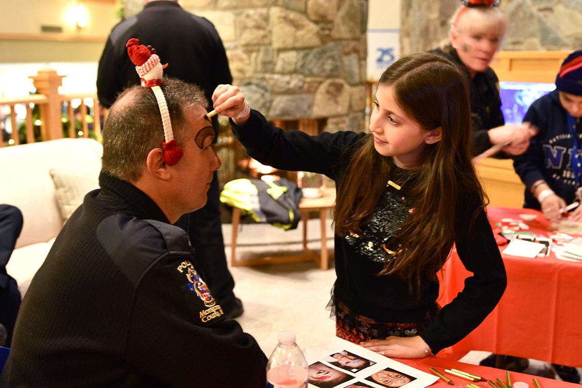 Child paints officer's face.