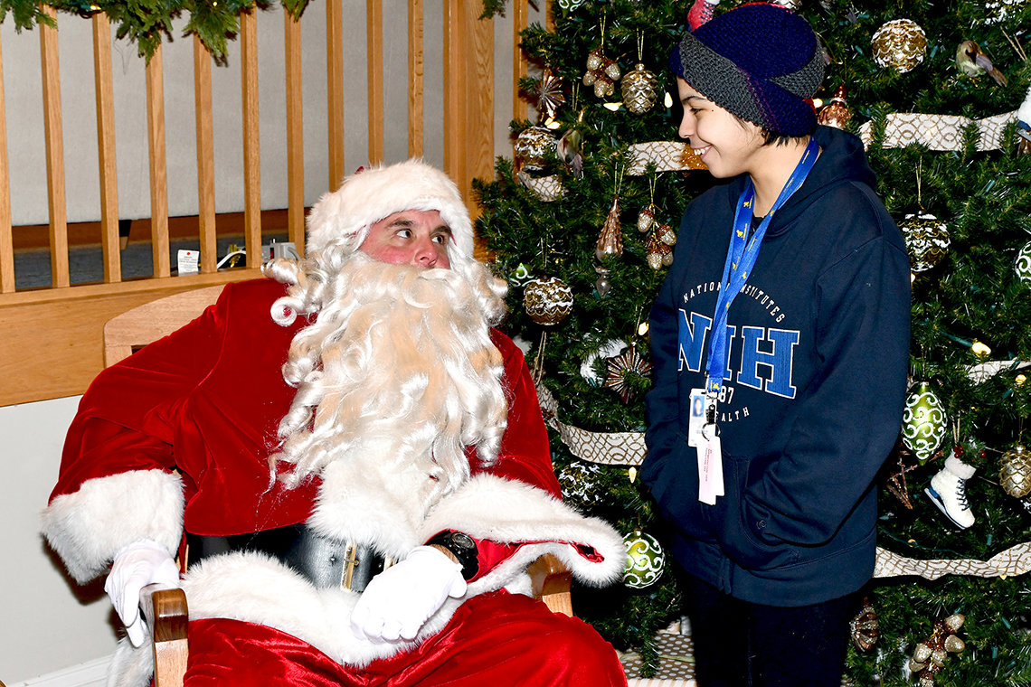 Santa talks with a teenager.