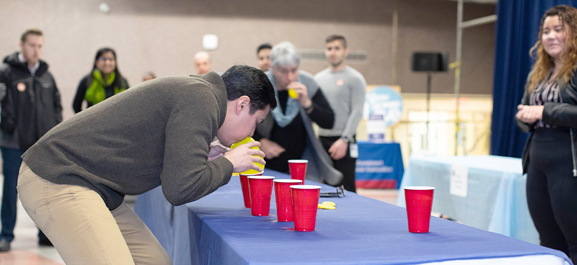 Flores blows air into a yellow balloon over red plastic cups on a table.