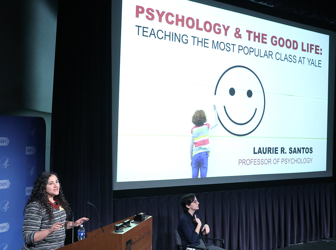 Santos stands in front of slide: Psychology and the Good Life, with a smiley face