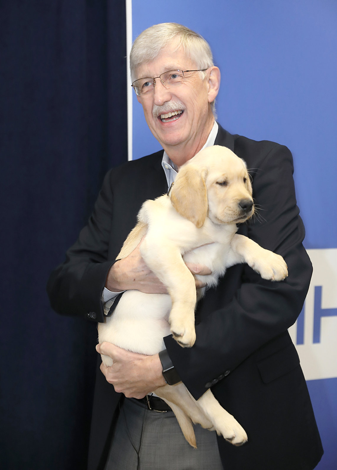 Smiling, Collins holds a puppy.