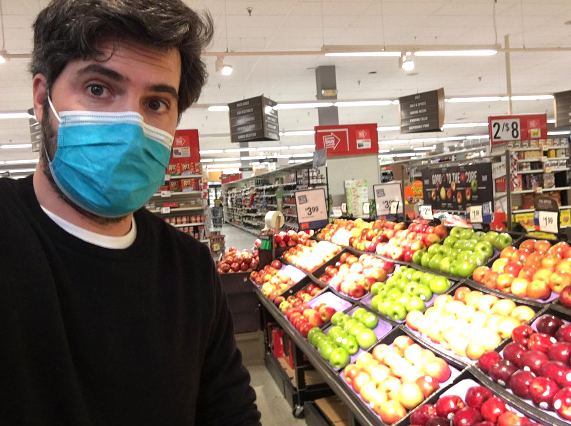 Wearing a mask, Vidal-Ribas stands in the produce section of a grocery store.