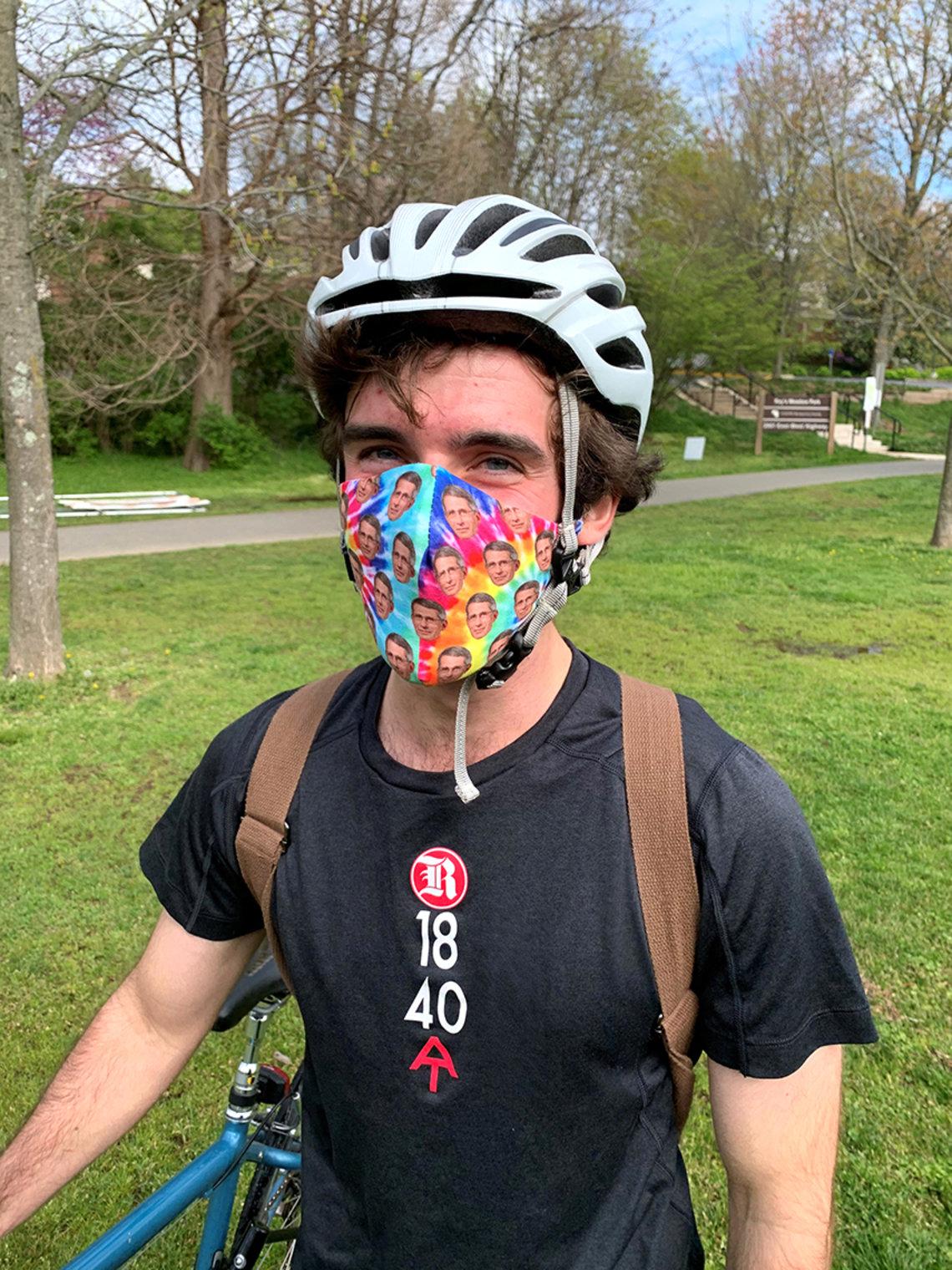 A man in a bike helmet wears a face mask