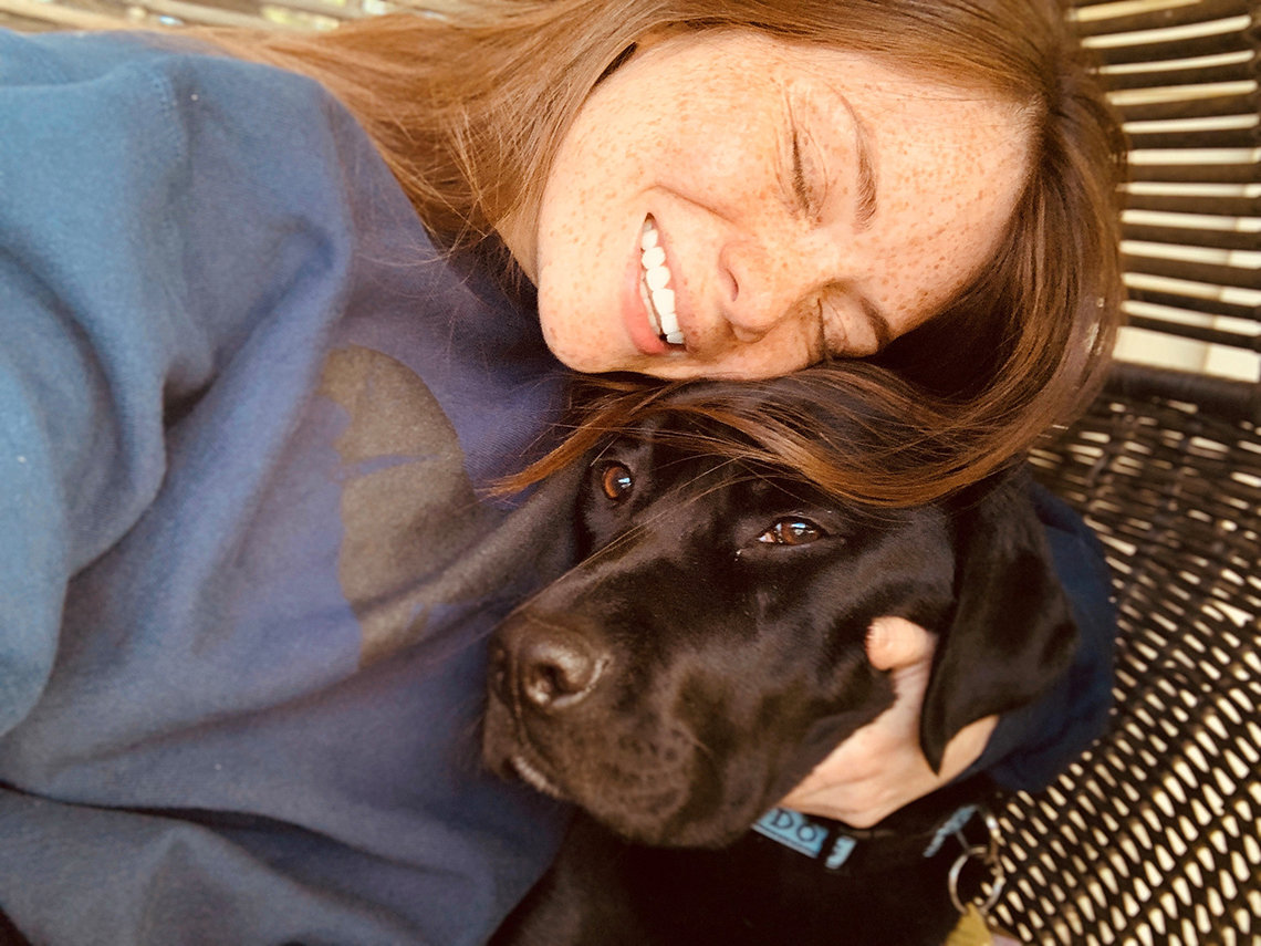 Woman cuddles pup.