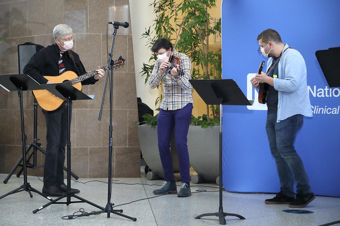 Three musicians play bluegrass music.