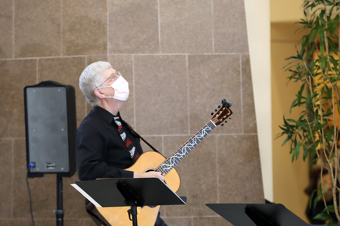 Dr. Collins looks to rafters as he holds guitar