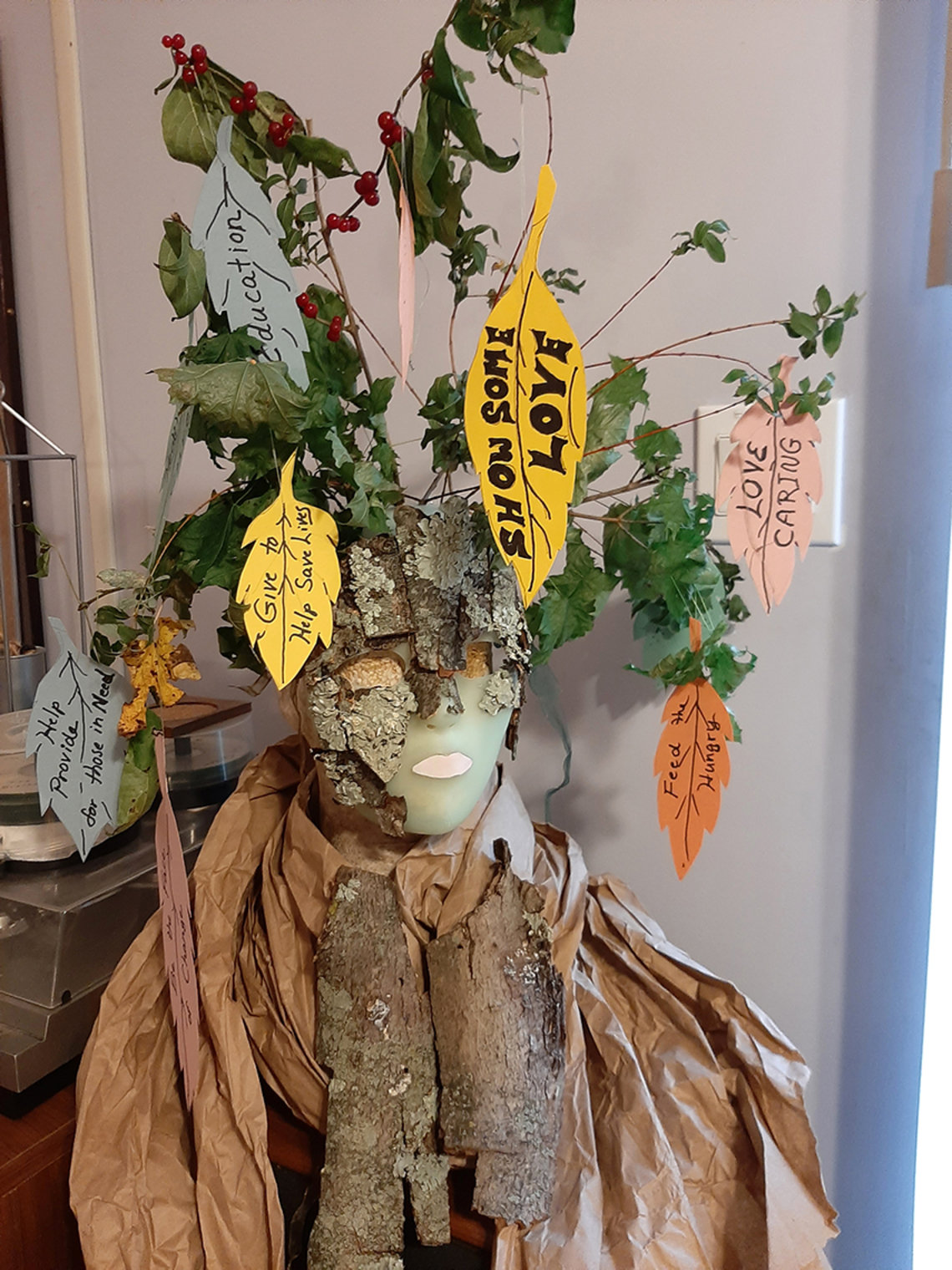 Mask called the Wishing Tree features branches with green leaves and handwritten tags