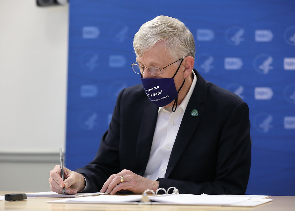 Dr. Collins writes notes at meeting.