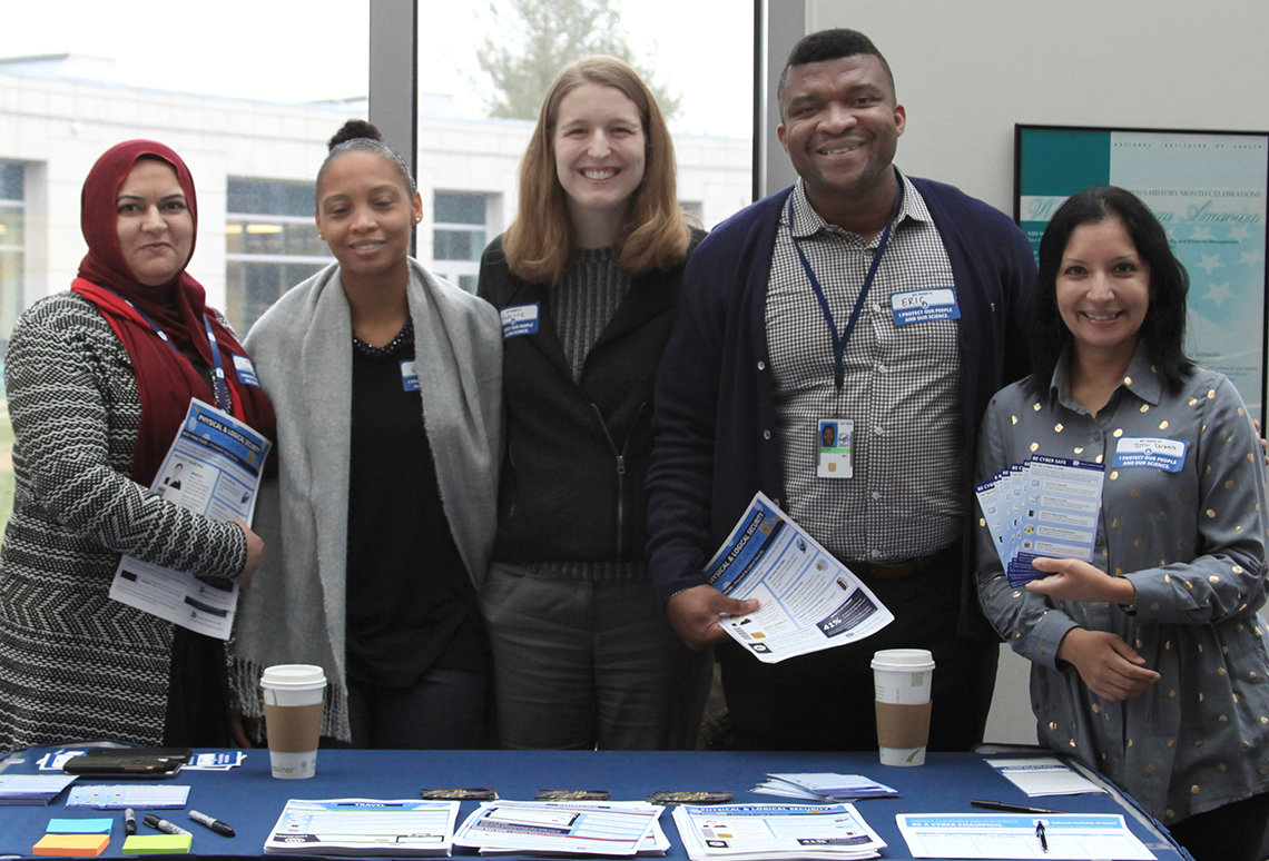 A smiling group of NIH'ers stand at an information table.